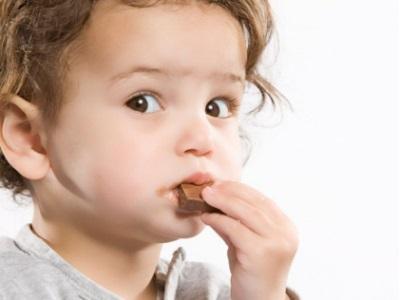Bambino che mangia una barretta di cioccolato