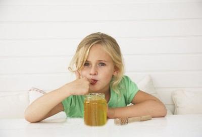 Bambino che mangia miele
