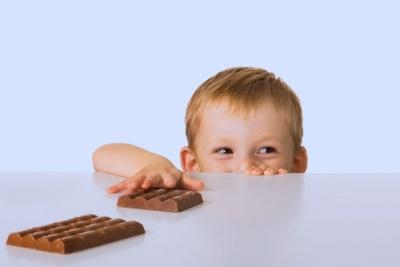 Het kind reikt naar chocolade