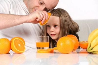 Vers sap van sinaasappel wordt bereid door een kind met papa