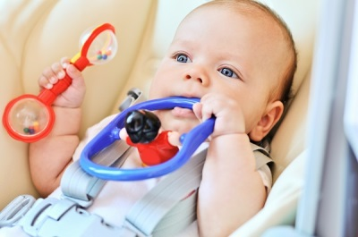 Bébé avec un hochet à 5 mois