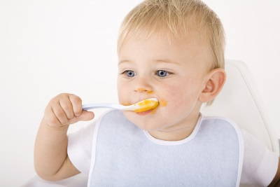El bebé come con una cuchara a los 11 meses.