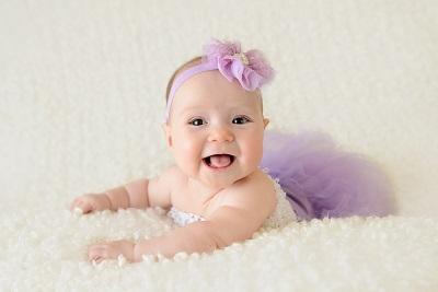 Baby bei 3 Monaten lächelnd - Mädchen im Kleid