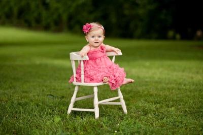 Un bebé de 9 meses está sentado en una silla.