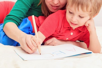 Seorang kanak-kanak belajar menulis huruf dan nombor.