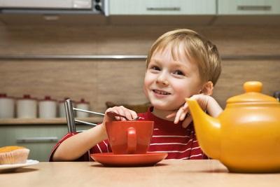 Baby aan tafel met thee