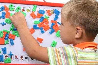 เด็กและกระดานแม่เหล็กด้วยตัวอักษร