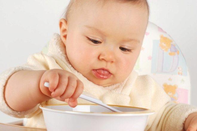 A criança come com uma colher
