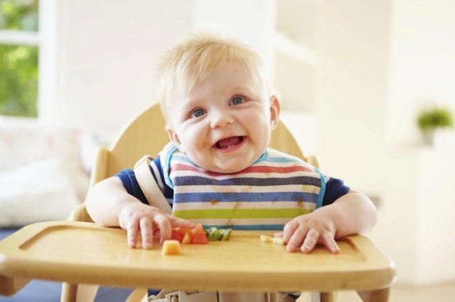 Bebê come em um ano em uma cadeira alta