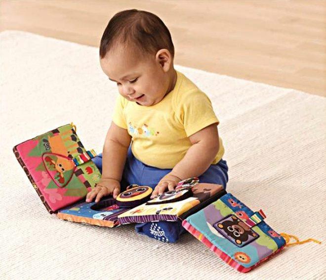 Uma criança está olhando para um livro de tecido.