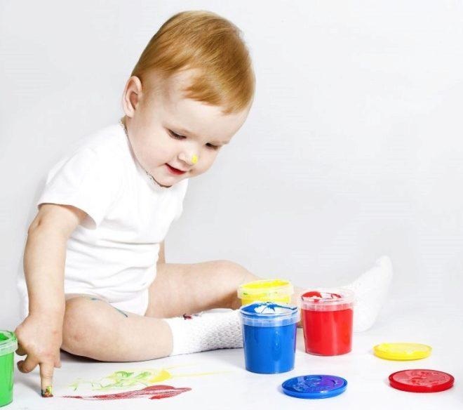 Uma criança em 1 ano desenha com pinturas a dedo