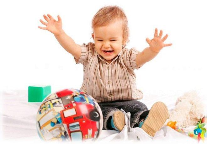 Uma criança 1 ano velha joga bola